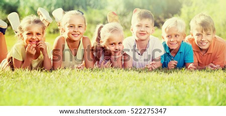 positive friends lying on green grass on bright summer day