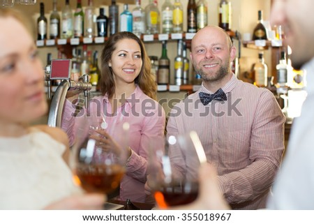 Positive happy bartender entertaining guests at a bar counter