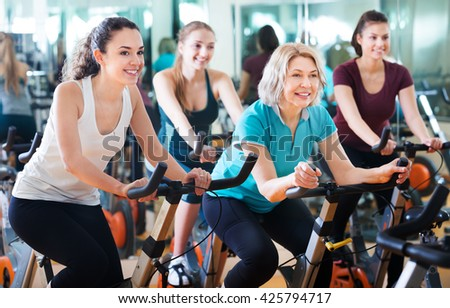 Positive happy females of different age training on exercise bikes together in fitness club