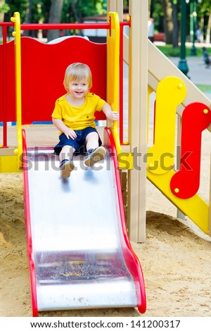 Positive little boy is about to go down from the slide on playground
