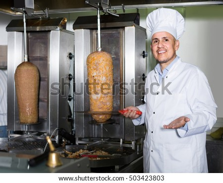 positive russian mature man chef wearing uniform cutting meat for kebab on kitchen in fast food restaurant