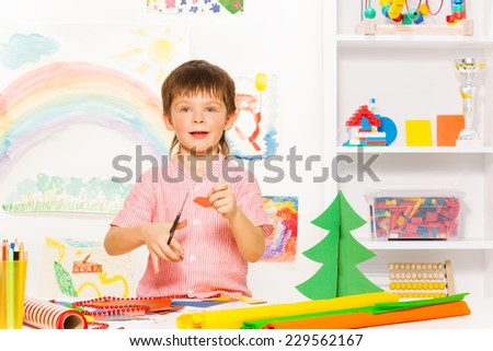 Positive small boy holding scissors and carton