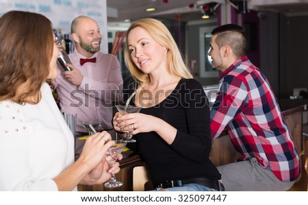 Positive smiling young adults hanging out in bar