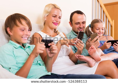 Positive young mom, dad and two happy kids working with smartphones indoors