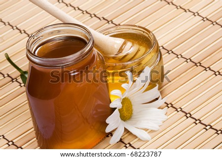 pots of honey and flower on wood