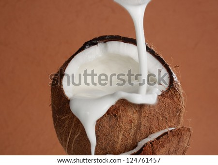 pouring coco milk from a can into fresh coconut