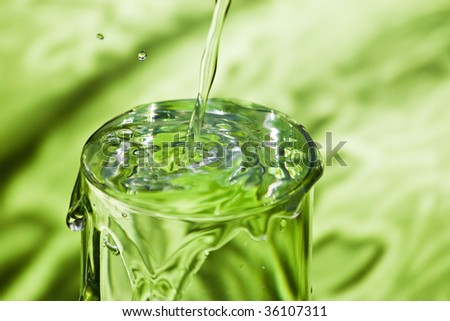 pouring water in full glass on green