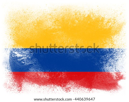Powder paint exploding in colors of Columbia flag isolated on white background. Abstract particles of colorful dust.