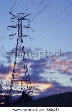 Power Lines and Tower - Birds perched on a transmission tower as the sun sets.