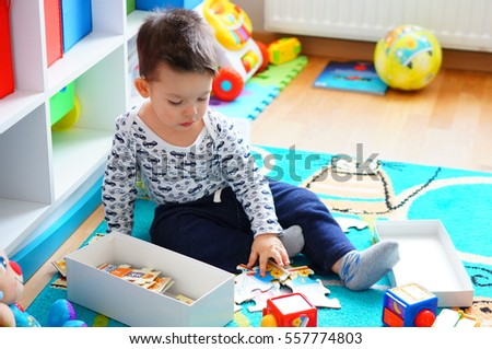 POZNAN, POLAND - FEBRUARY 28, 2016: Two years old unidentified boy playing with wooden brand train puzzle on a floor
