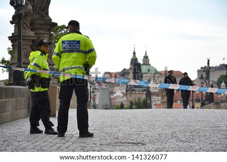 PRAGUE, CZECH REPUBLIC - JUNE 5: Police patrol guarding the Charles Bridge on June 5, 2013 in Prague, Czech republic. Prague declared a state of emergency as the flooding  tore into the city.