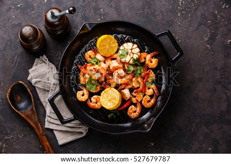 Prawns Shrimps roasted on frying grill pan with lemon and garlic on dark background