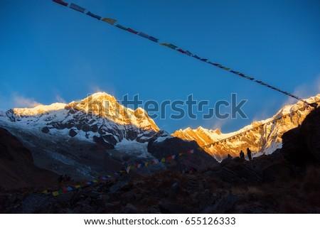 Snow mountain range tibetan prayer flags stock photo 243328114 prayer flags and mt annapurna i background from annapurna base camp nepal sciox Choice Image