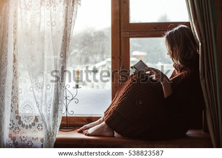 Pre teen child in warm woolen sweater seating on window sill and reading a book. Winter weekends in old log house. Cold snowy weather. Cozy homely concept.