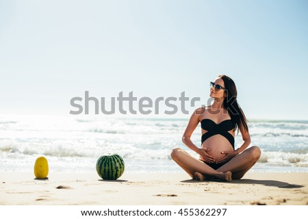 Pregnant and fruits on the beach. Pregnant and fruits near the sea. Fruit composition and the expectant mother. Fruit holiday or vacation.