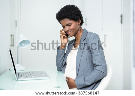Pregnant businesswoman on the phone in the office