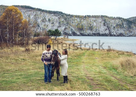 pregnant girl and her husband standing next to the horse near the river
