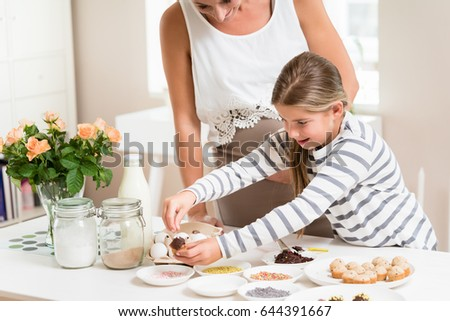 Woman Decorating Cupcakes pregnant mum her little daughter baking stock photo 483749908