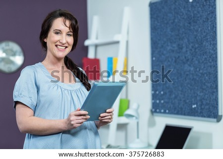 Pregnant woman holding tablet at home