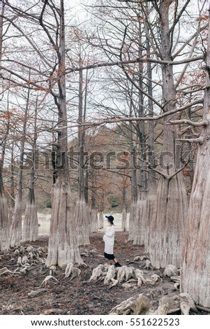 pregnant woman in park on a background of trees