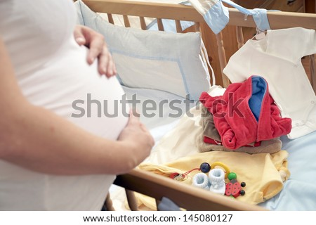 pregnant woman in the childrens room with baby stuff / baby room