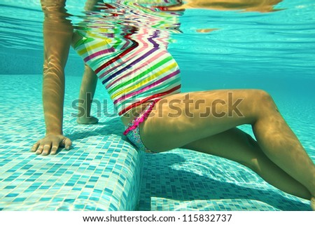 Pregnant woman in the pool in the bright striped swimsuit