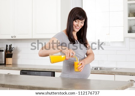 Pregnant woman pouring glass of orange juice in kitchen