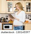pregnant woman using a tablet computer in kitchen - stock photo