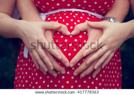 Pregnant woman with her hands on her belly