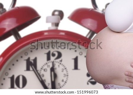 pregnant woman with naked belly and alarm clock / pregnancy