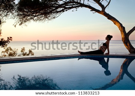 Pregnant young woman by the pool at sunrise