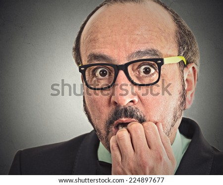 Preoccupied middle aged man. Closeup portrait nerdy guy with glasses biting his nails looking at you craving something anxious isolated grey wall background. Human face expression emotion feeling
