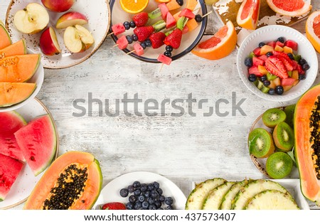 Preparing a healthy fruit salad on white wooden  background. Top view