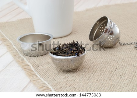 preparing a tea, filled the tea strainer with a chain on burlap