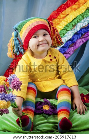 Preschool girl on the rainbow background with flowers