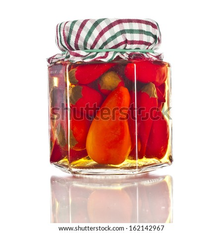 preserved red hot pepper  with reflection  in glass jar close up isolated on a white background