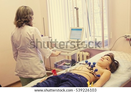 preteen boy under ecg test with doctor close up photo