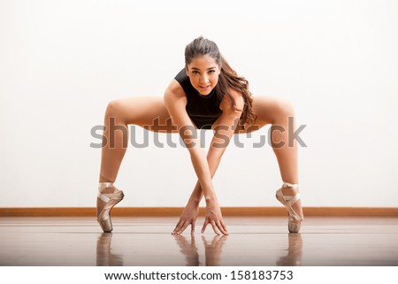 Pretty and strong female ballet dancer holding on a pose during a rehearsal in a dance studio