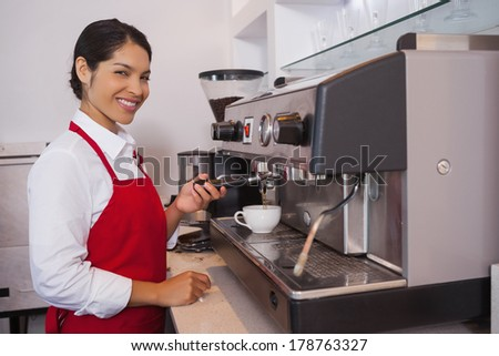 Pretty barista making coffee smiling at camera in a cafe