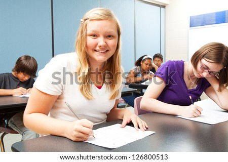 Pretty blond girl sitting in her high school class.