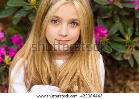 Pretty blond girl sitting in the flowers looking at you