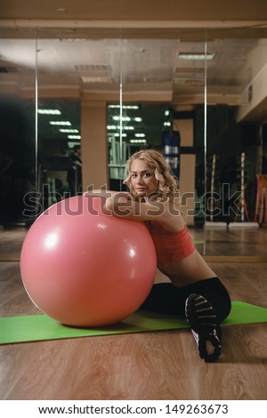 Pretty blond girl stretching muscles in gym
