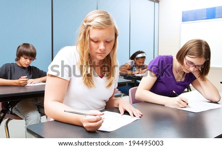 Pretty blond girl taking a test with her high school class.