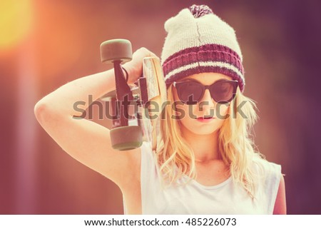 Pretty blond teen girl holding skateboard