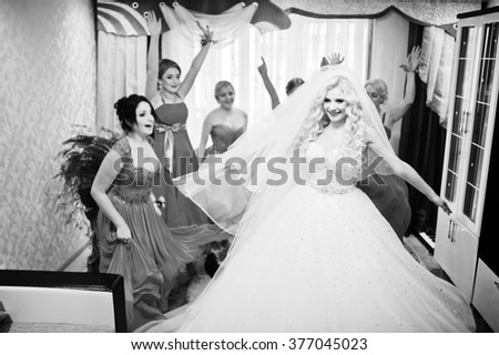 Pretty blonde bride with four magic bridesmaids having fun at room. Charming wedding day