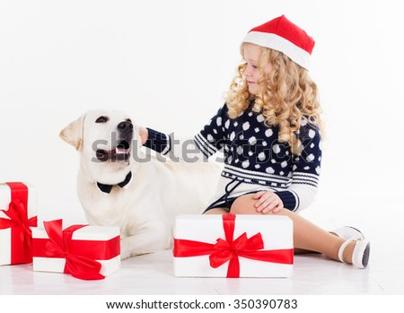 Pretty blonde child girl with her friend white labrador retriever are wearing christmas hats and sitting with gifts isolates on white in studio