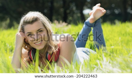 Pretty blonde lying on grass with headphones around neck on a sunny day in the countryside