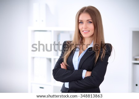 Pretty brunette business lady in the office in a black   jacket, crossed arms