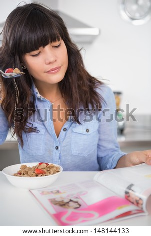 Pretty brunette eating cereal and reading magazine at home in kitchen