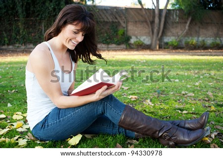 pretty brunette girl reading book in park